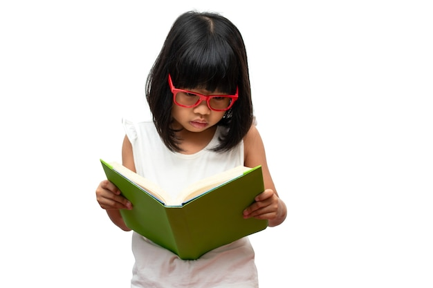 Счастливая азиатская маленькая девочка дошкольного возраста в красных очках, держащая и читающая зеленую книгу на белом изолированном фоне. концепция школьника и образования в начальной и дошкольной, домашней школе