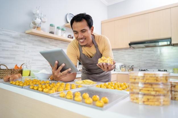 若い男の幸せなアジア人男性の自家製ケーキの肖像画は、プラスチック容器の箱にnastarケーキを置きます