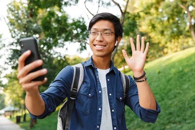 Happy asian male student in eyeglasses making selfie on smartphone and waving at camera while being in park
