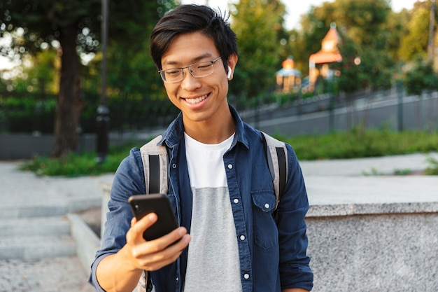 屋外でスマートフォンを使用して眼鏡とイヤホンで幸せなアジアの男子学生