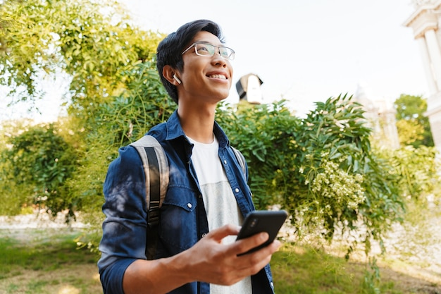 スマートフォンを保持し、屋外を見て眼鏡で幸せなアジアの男子学生