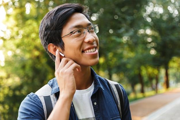 Счастливый азиатский студент-мужчина в очках слушает музыку и смотрит в сторону