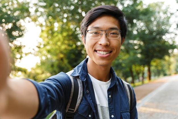 自撮りをして、屋外でカメラを見ている眼鏡の幸せなアジアの男子学生