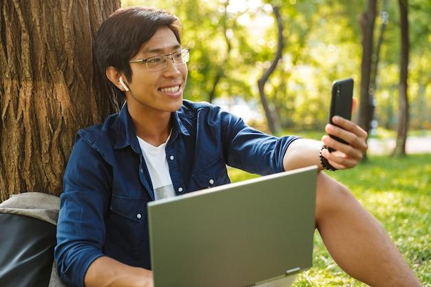 スマートフォンでselfieを作り、公園の木の近くに座っている間ラップトップを保持している眼鏡の幸せなアジアの男子学生