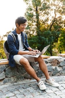 公園のベンチに座っている間ラップトップコンピューターを使用して眼鏡で幸せなアジアの男子学生