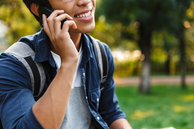 公園に座ってスマートフォンで話す幸せなアジアの男子学生