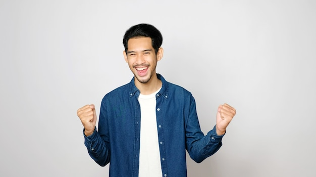 Happy asian man arm up with successful achievement looking at camera while standing over isolated grey background