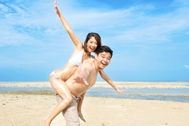 Happy asian man carrying a girl on his back in the beach