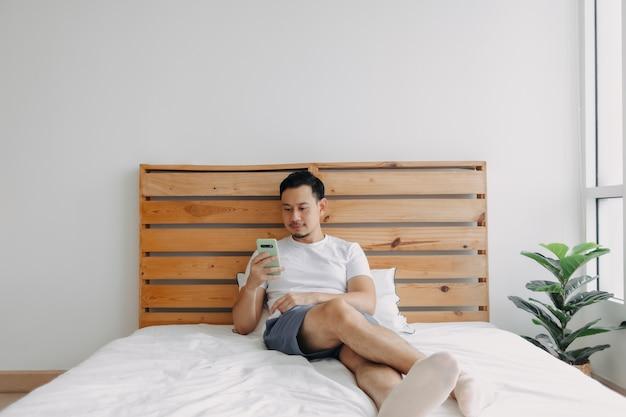 행복 한 아시아 사람이 자신의 침대에서 스마트 폰으로 휴식을 느낀다