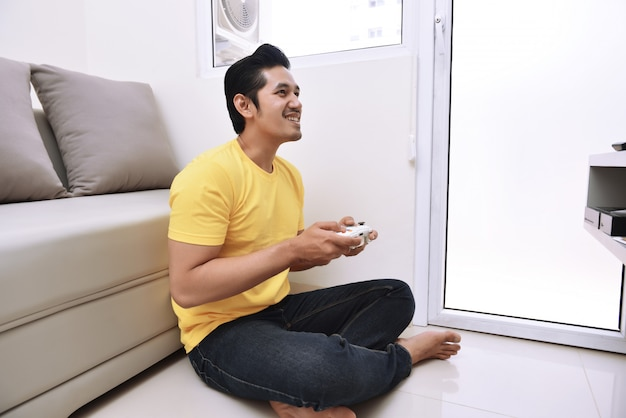 Happy asian man holding gamepad and playing video games