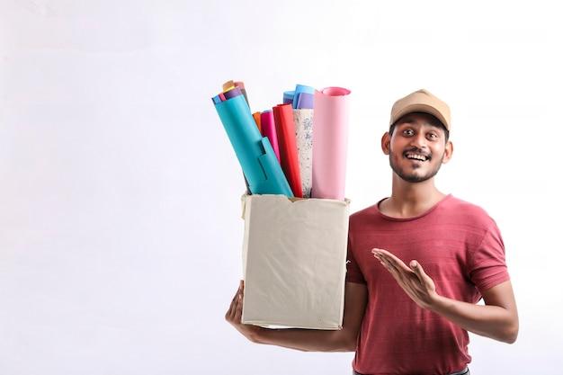 Tシャツと白い背景で隔離の色の紙箱、配達サービスの概念を保持している帽子の幸せなアジア人男性