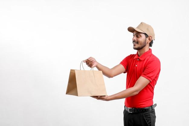 白い背景の上に分離された空のボックスを保持しているtシャツと帽子の幸せなアジア人、配達サービスの概念