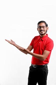 Tシャツを着て、白い背景で隔離の表情を示す幸せなアジア人。