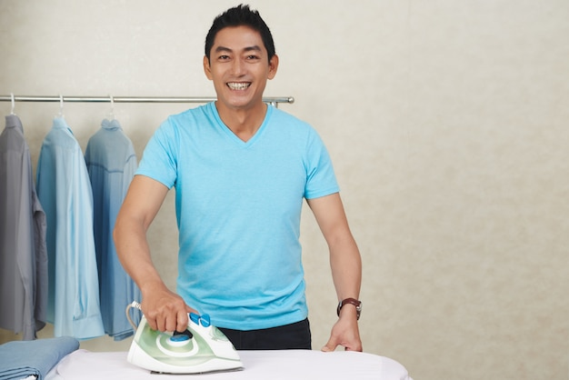 Happy asian man ironing clothes at home