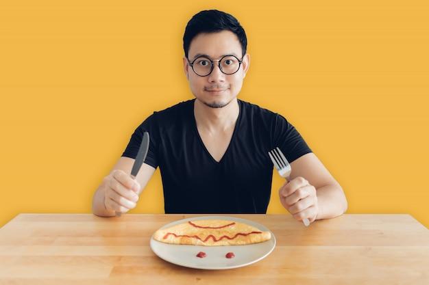 행복 한 아시아 사람은 오믈렛의 수 제 아침 식사 세트를 먹고있다.