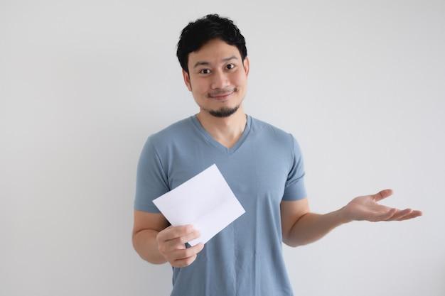 幸せなアジア人男性は、孤立した白い壁に請求書の手紙を持っています。