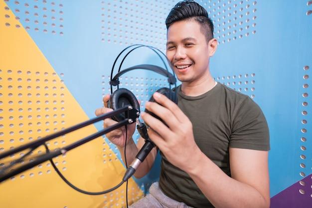 幸せなアジア人男性が彼のスタジオでポッドキャストを録音しています