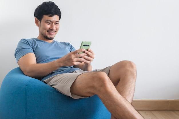 幸せなアジア人男性は、ビーンバッグに座ってリラックスしながらスマートフォンを使用しています。