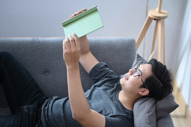 Счастливый азиатский человек кладя на удобный диван и читая книгу.