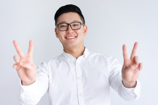 Happy asian man showing two victory signs