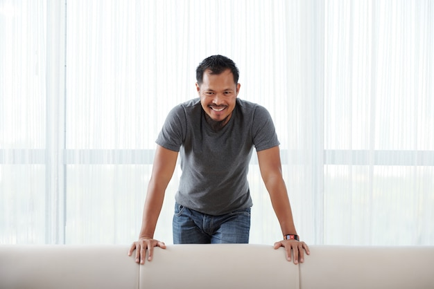 Happy asian man standing behind couch, leaning on it and smiling for camera