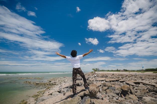 푸른 하늘이 있는 바위 해변에 서 있는 행복한 아시아 남자