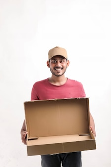 Happy asian man in t-shirt and cap holding empty box isolated over white background, delivery service concept