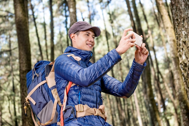 Happy asian man taking pictures of forest