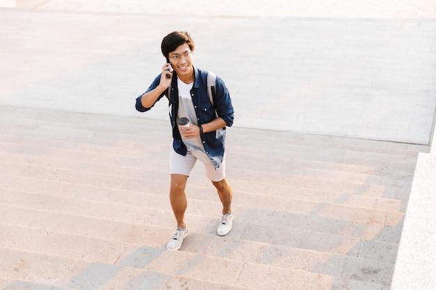 커피 한잔과 함께 야외에서 위층을 걷는 동안 휴대 전화에 얘기하는 행복 한 아시아 사람