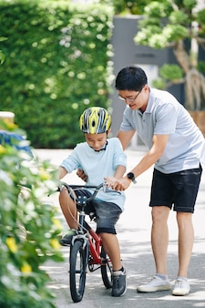 Happy asian man teaching preteen son in helmet riding bicycle in house backyard