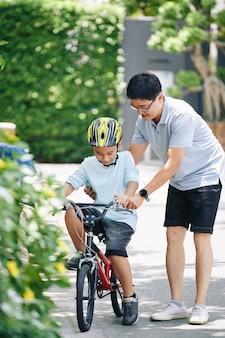 家の裏庭で自転車に乗ってヘルメットでプレティーンの息子を教える幸せなアジア人