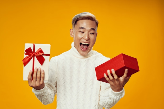 Happy asian man in warm winter clothes opening a present