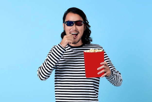 Happy asian man wearing 3d glasses and eating popcorn while watching movie.