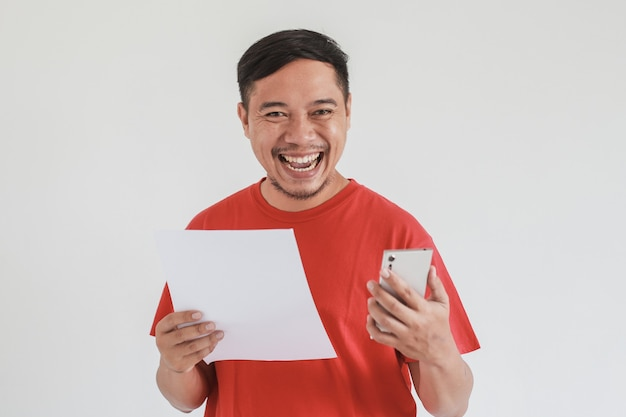 白い白紙とスマートフォンを保持しながら赤いtシャツ探しカメラを身に着けている幸せなアジア人男性