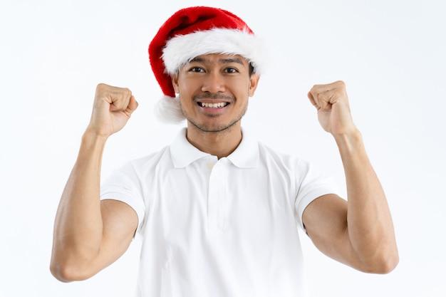 Happy asian man wearing santa hat and pumping fists