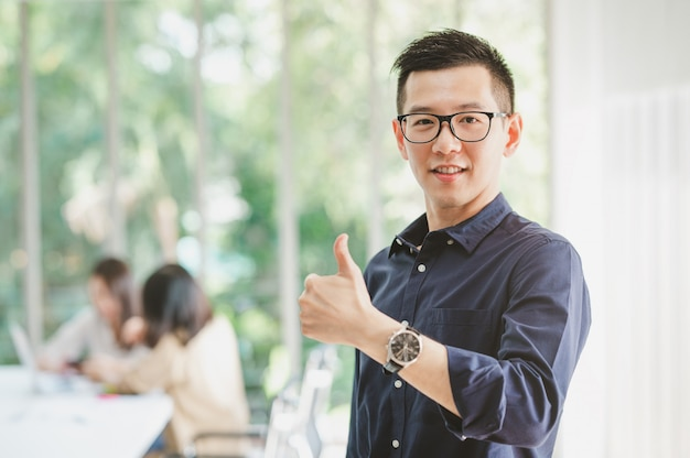 Happy asian man with thumbs up with colleague