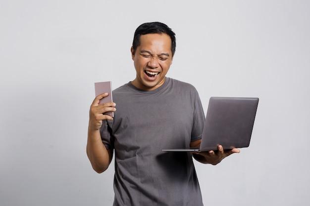 노트북과 스마트 폰을 들고 승리 제스처와 함께 행복 한 아시아 남자