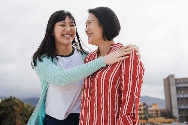 幸せなアジアの母と娘が屋外で抱き締めることを楽しんでいます-年配の女性の顔に焦点を当てる