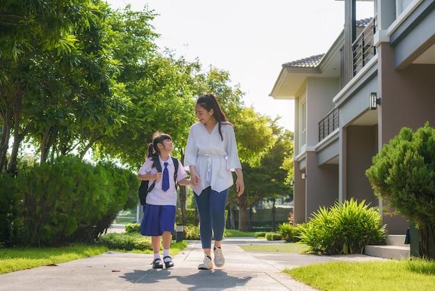 Счастливый азиатский ученик начальной школы матери и дочери идет в школу в утреннем школьном распорядке в течение дня в жизни, готовясь к школе.