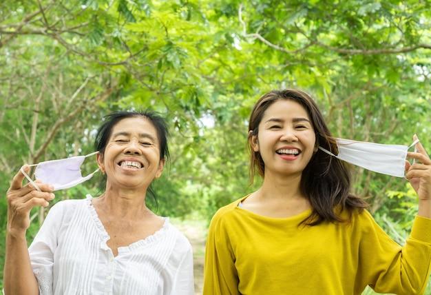 행복 한 아시아 어머니와 딸이 얼굴 마스크와 함께 야외에서 여행