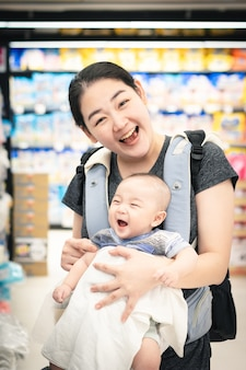 Happy asian mother and baby laugh in supermarket, sell and shopping, online, e-commerce,