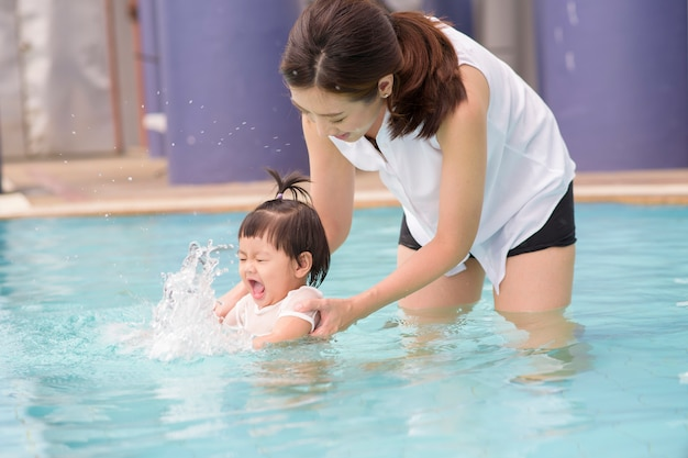 A happy asian mother and daughter are enjoy swimming in pool , lifestyle, parenthood, family concept .