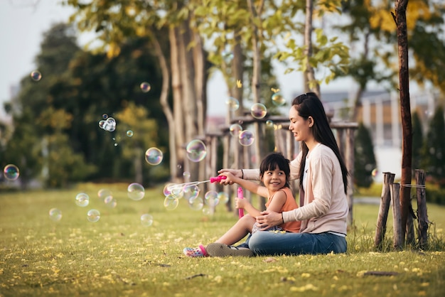 Happy asian mother and daughter blowing bubbles in park outdoors