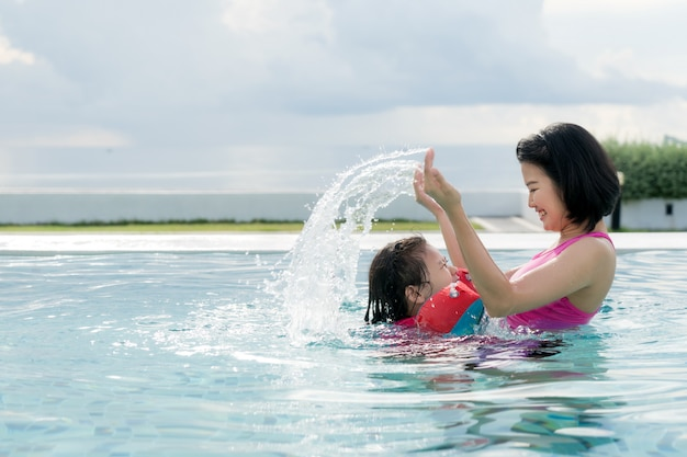 Happy asian mother and daughter having fun in hotel swimming pool