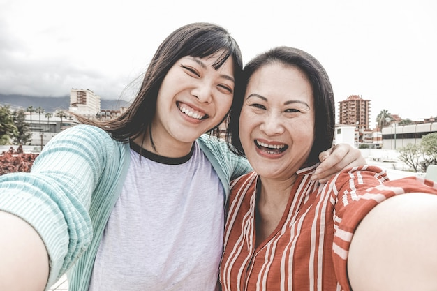 Happy asian mother and daughter taking selfie portrait photo for mother's day fest