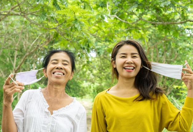 Happy asian mother and daughter traveling outdoors with face mask