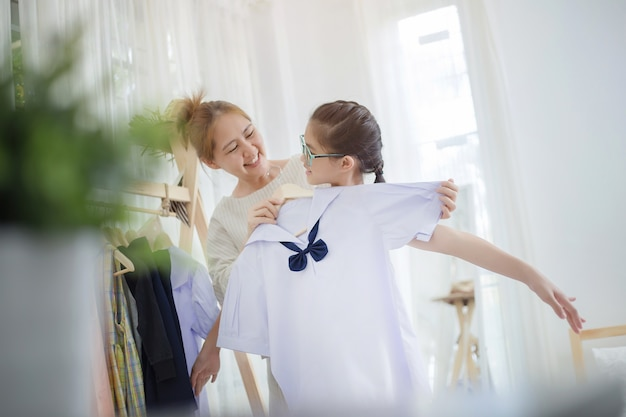 Happy asian mother helping daughter dressing her's uniform prepare to school, back to scho