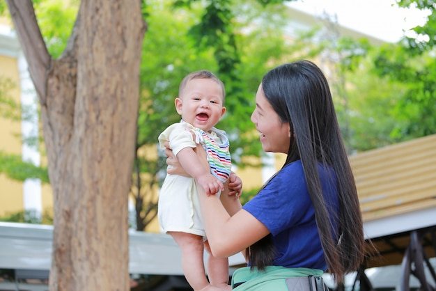 Happy asian mother holding her infant in arms at green garden.