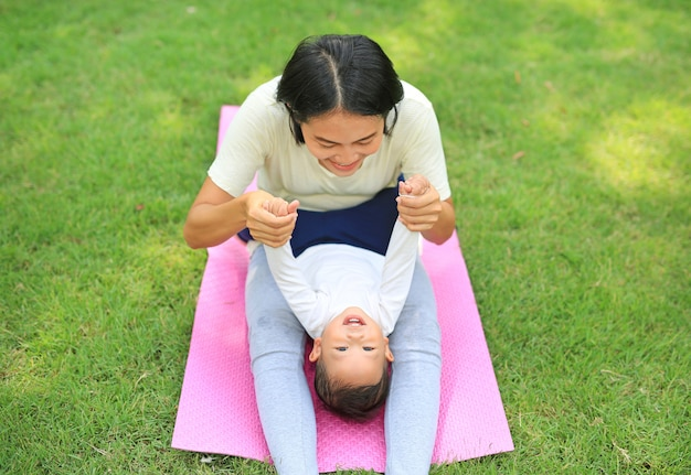 Happy asian mother playing with her son and lying on green lawn at park.