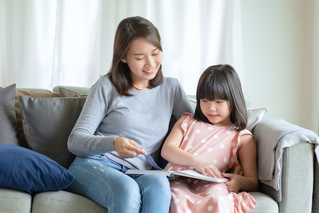 Happy asian mother teaching her cute kid daughter to studying in living room at home
